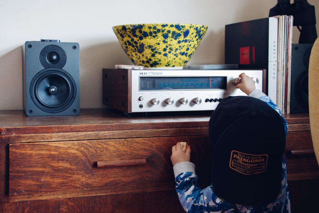 Kleines Kind geht an die Stereo-Anlage seiner Eltern