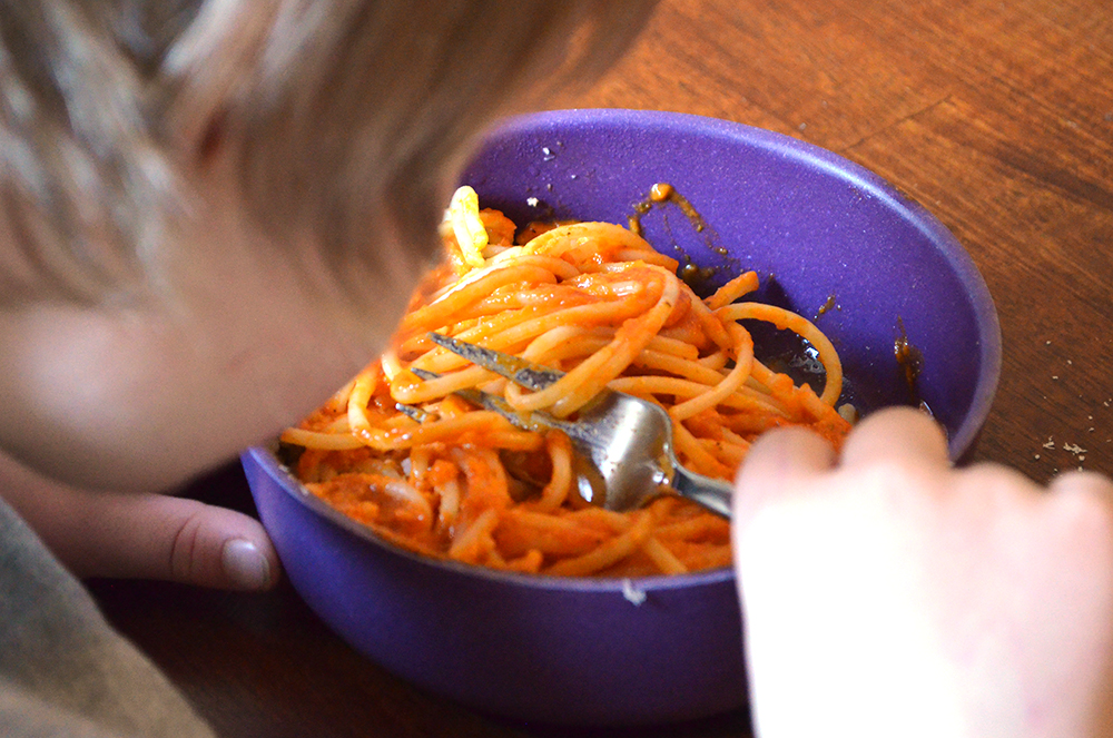 Kind isst Spagetti mit Tomatensoße