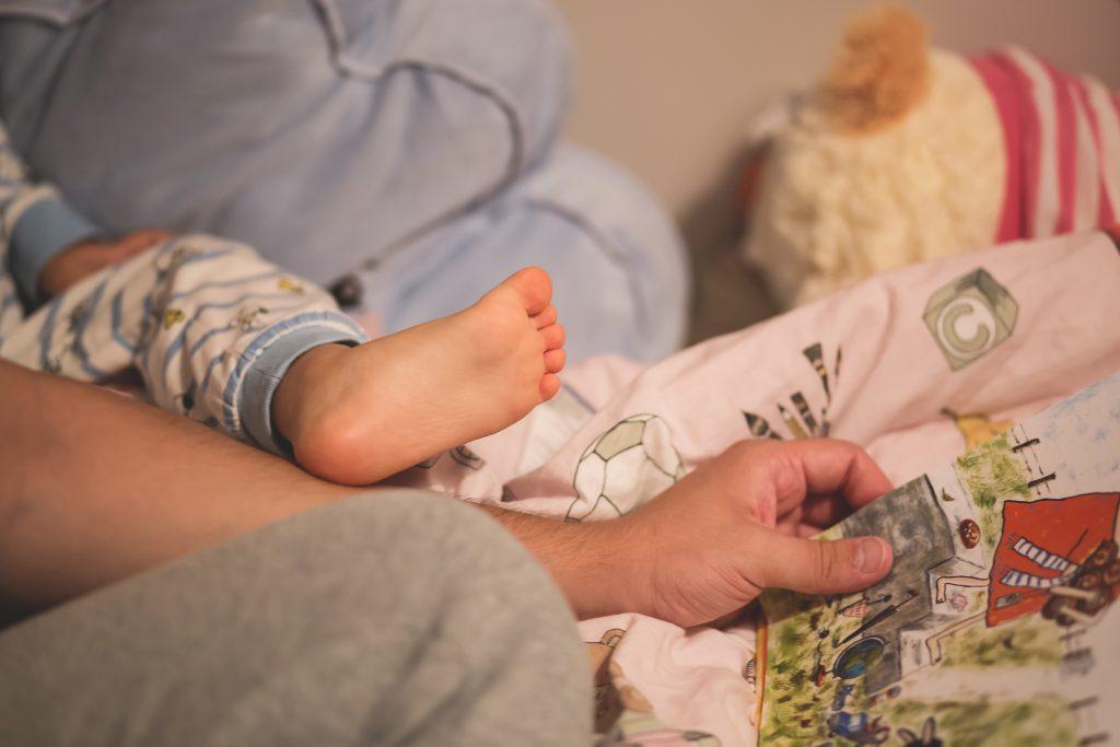 Elternteil bringt Kind ins Bett.