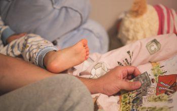 Elternteil bringt Kind ins Bett