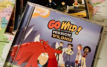 drei go wild cds liegen auf einer schreibtischunterlage, die eine Weltkarte zeigt