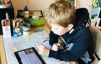 junge sitzt an seinem Schreibtisch und macht homeschooling wegen corona