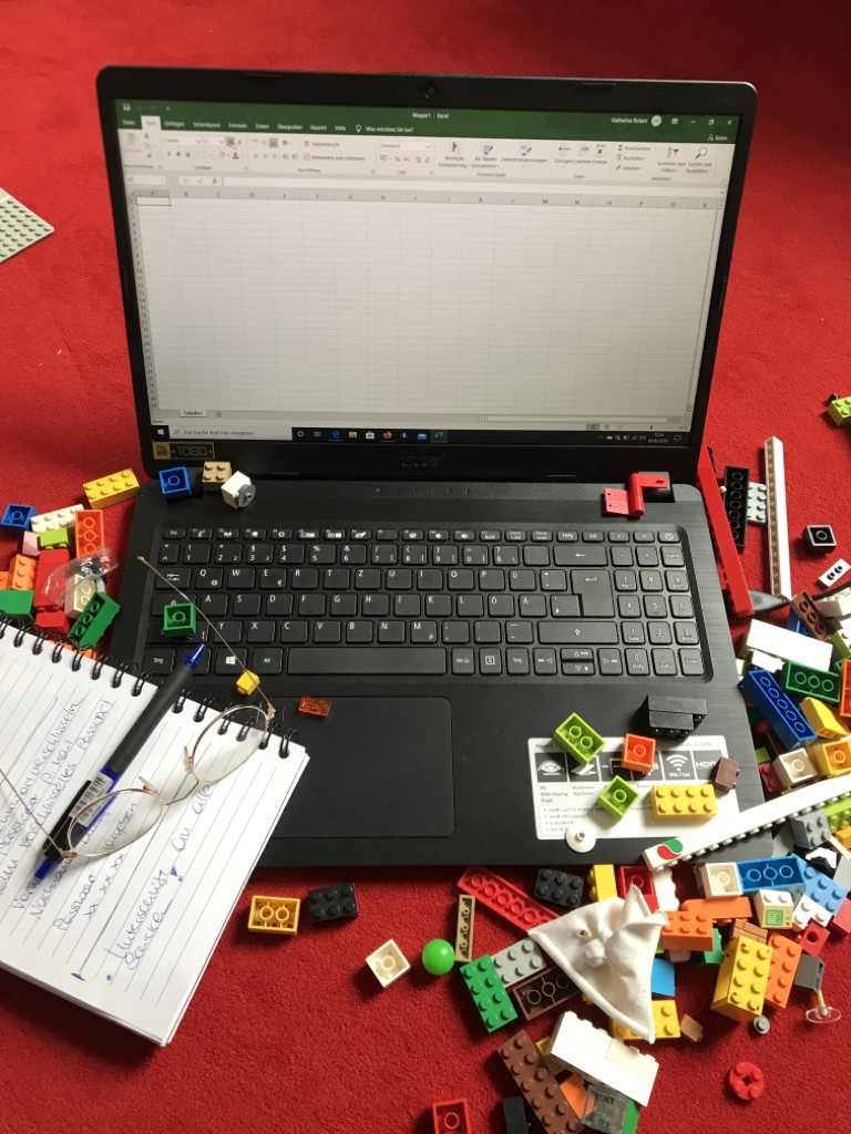 Laptop, Notizblock und Brille zwischen Legosteinen.